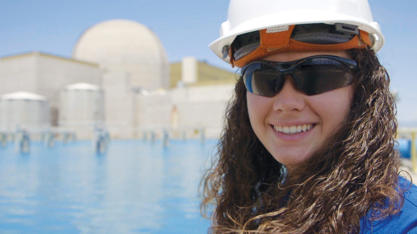 APS employee in protective glasses and a hard hat smiling in front of Palo Verde.