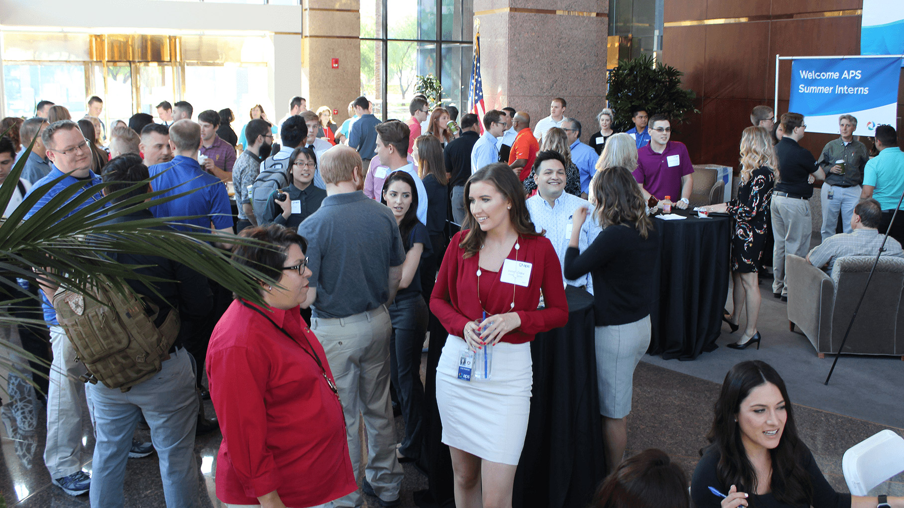 APS interns and employees talking at the summer internship welcome event.