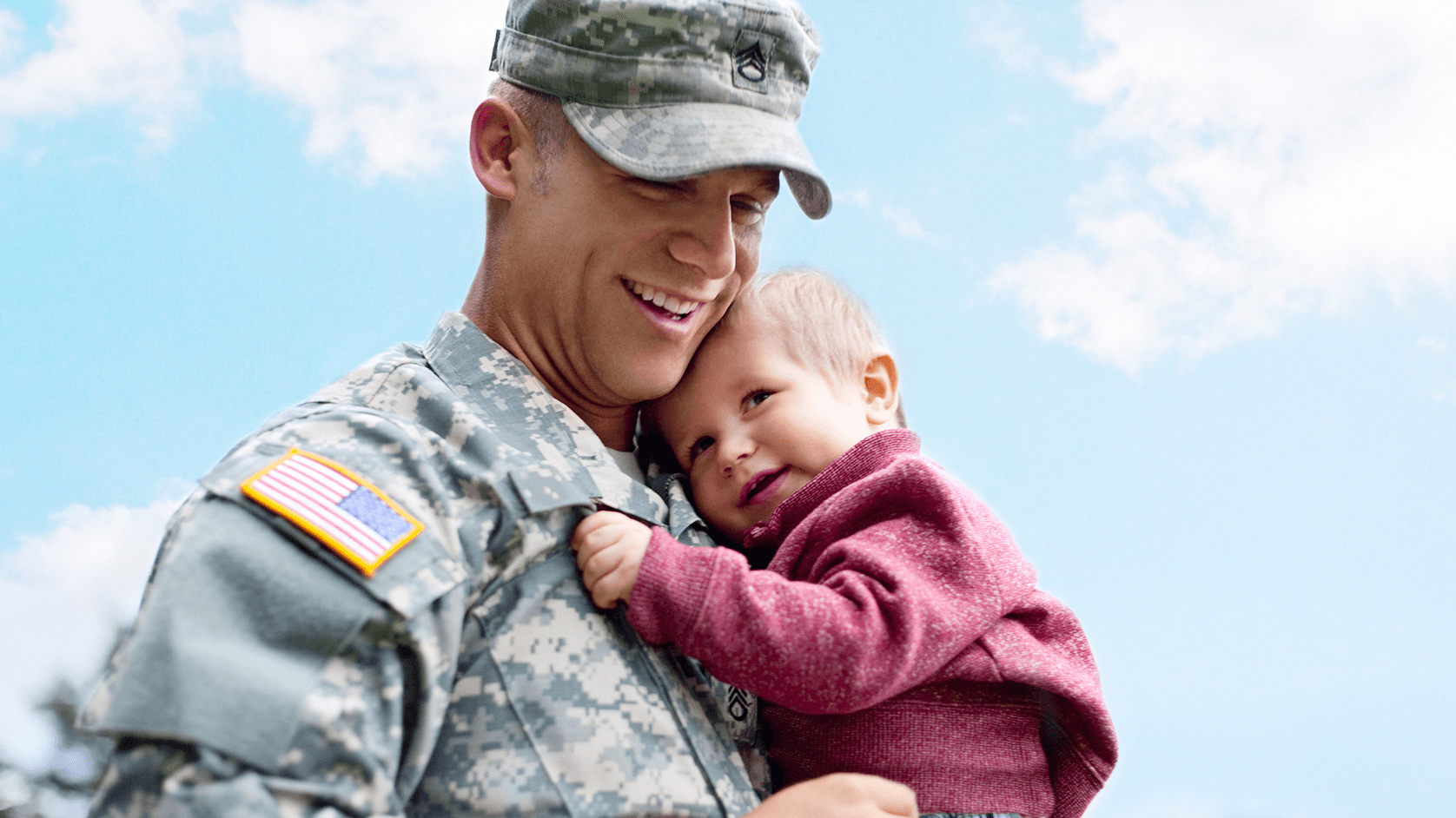 U.S. service member smiling and holding his daughter.