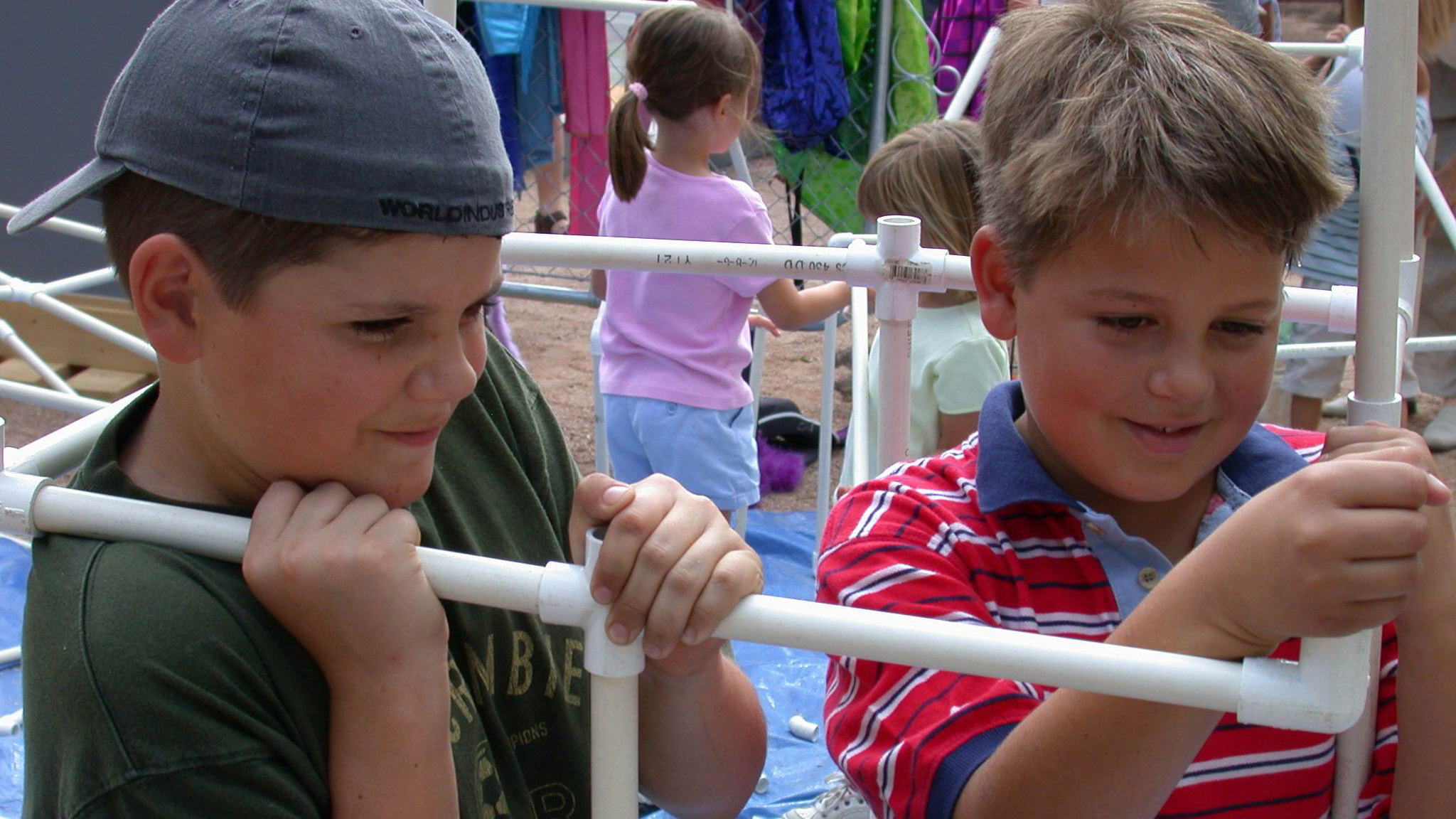 Two young kids working with PVC pipe.