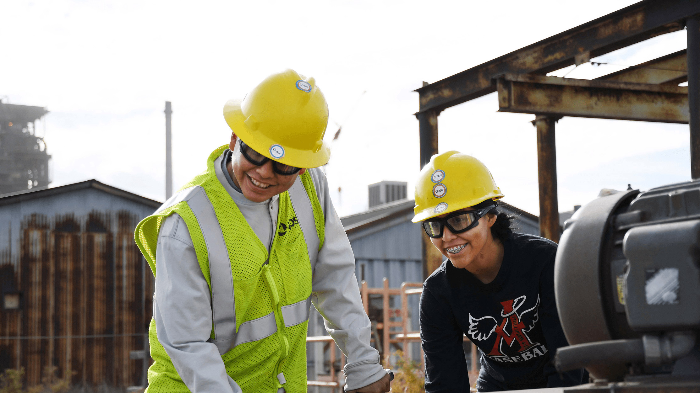 Two APS employees smiling while working at a power plant.