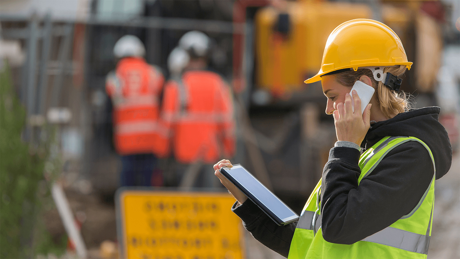 Construction worker talking on her phone at a construction site.