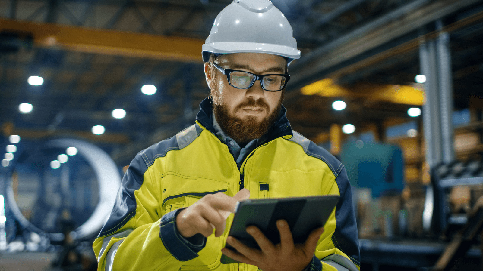 Man in a warehouse facility wearing a hard hat looking at a tablet.