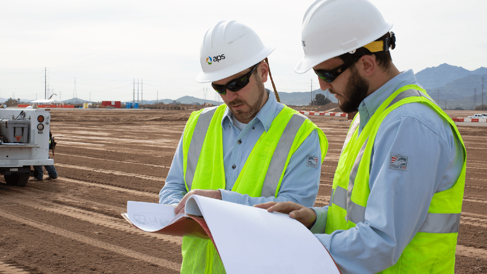 Two APS employees looking at blueprints.