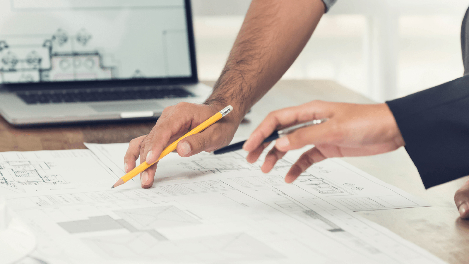 Two people working on blueprints.