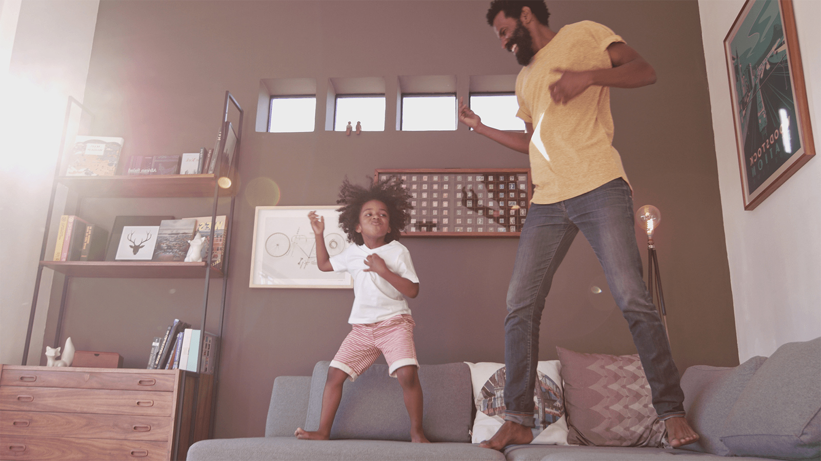 Father and his daughter playing air guitar on the couch.