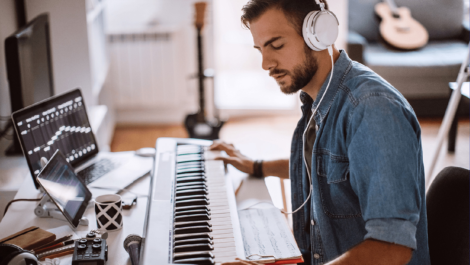 Man with headphones and using a keyboard piano.