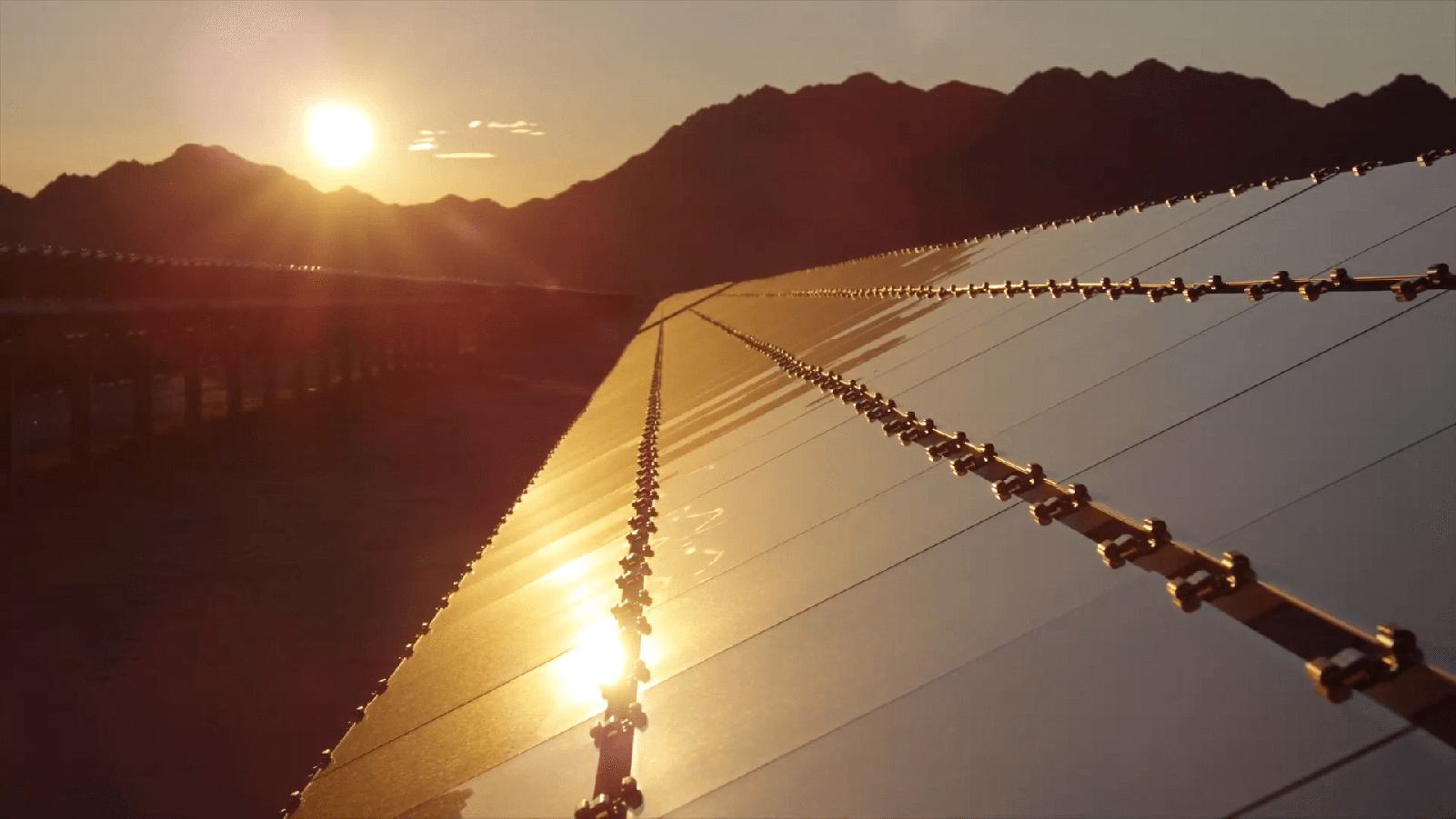 Paloma Solar Plant with a mountainscape and setting sun.