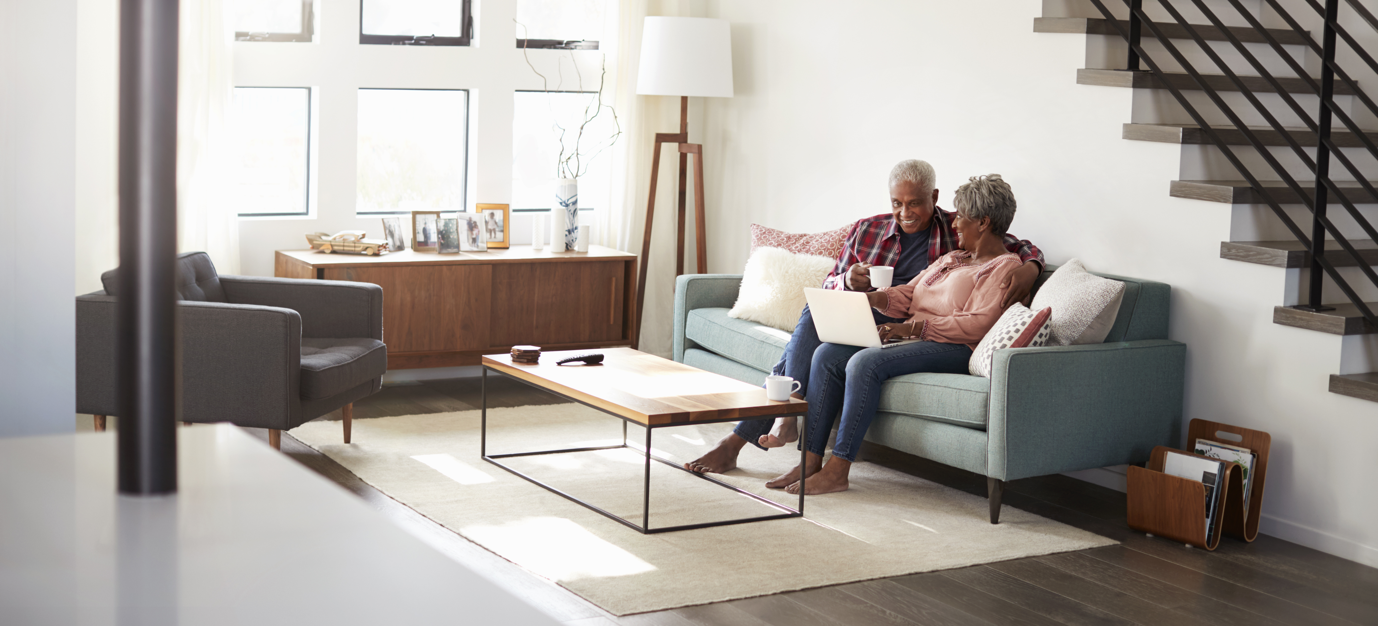 Man and woman sitting on couch in their house