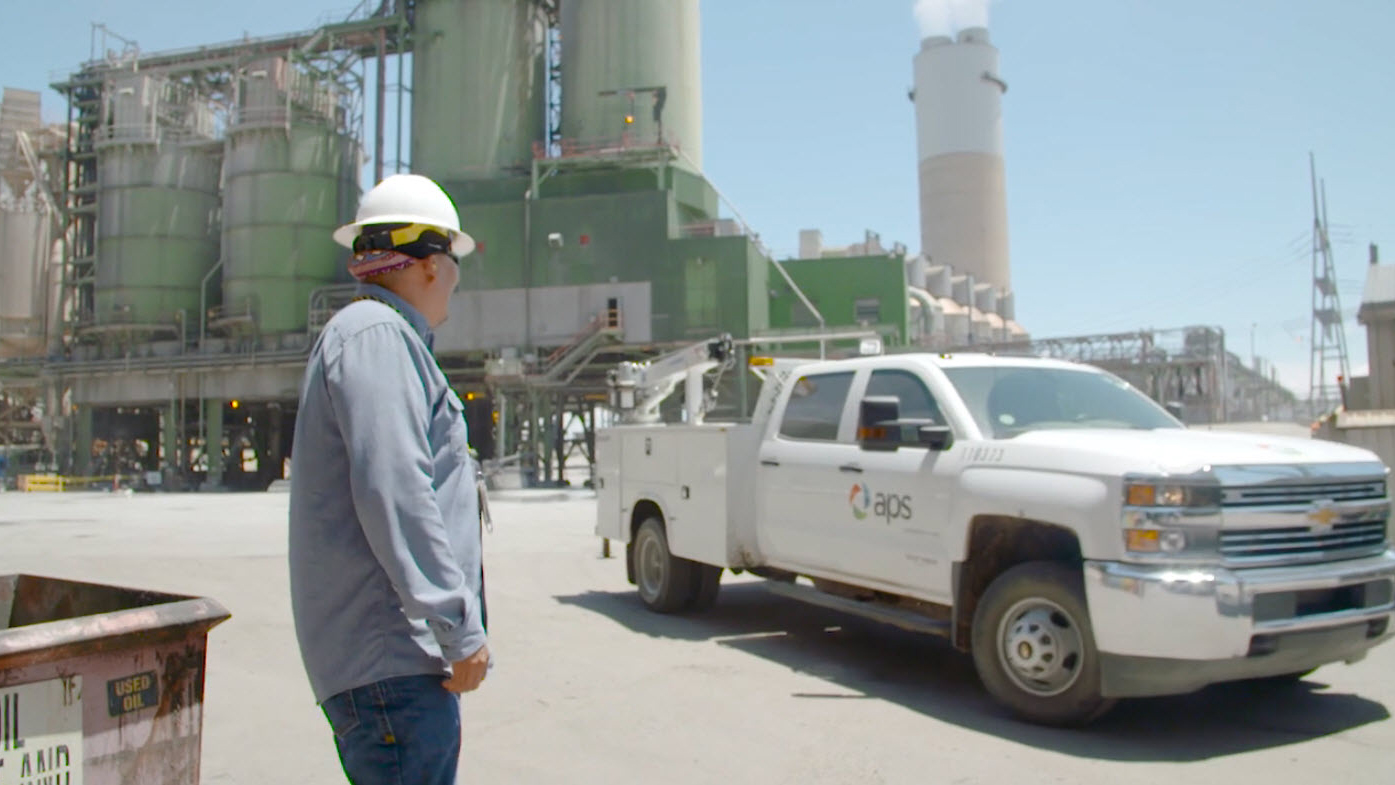 Employee stands outside at the Four Corners Power Plant with APS work truck driving by
