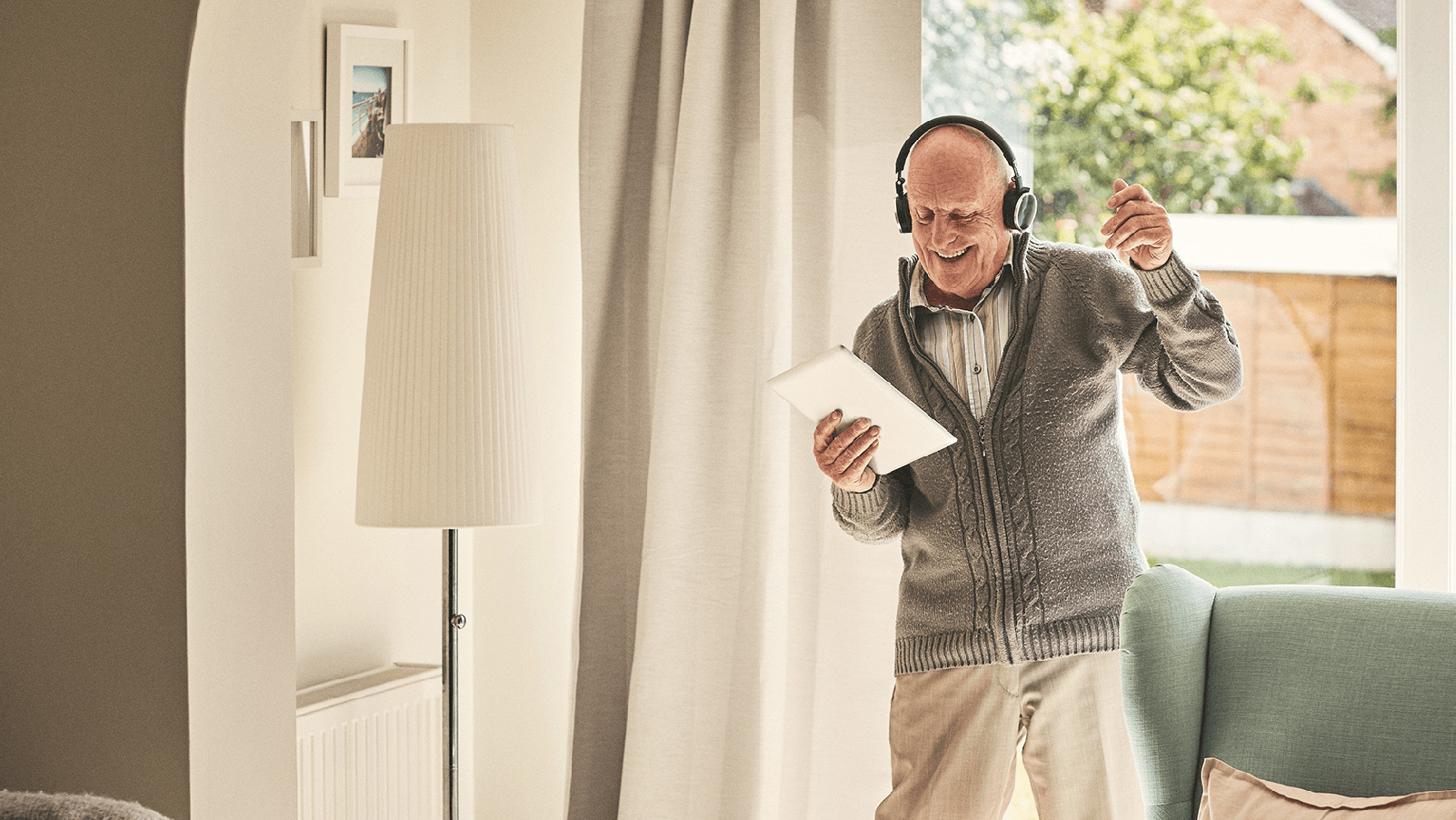 Man holding tablet and wearing headphones dancing in living room.