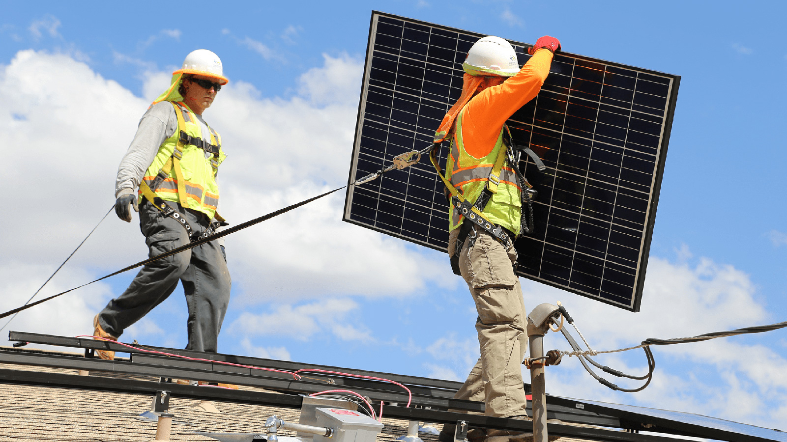 Two people installing rooftop solar panels.