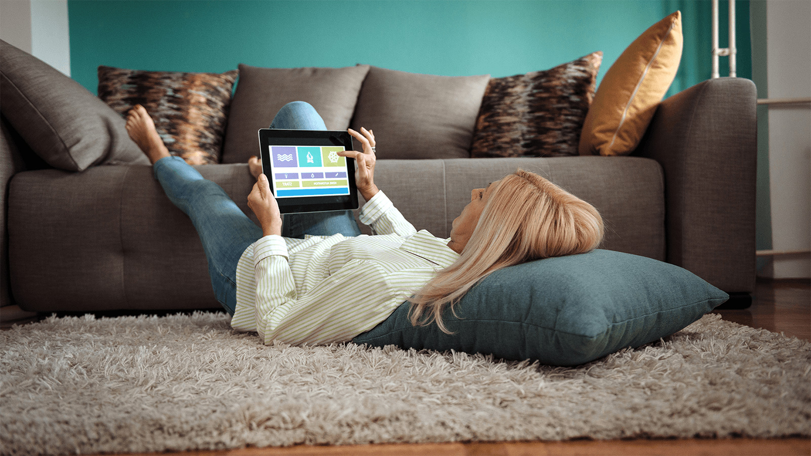 Woman relaxing on her living room floor and using her tablet.