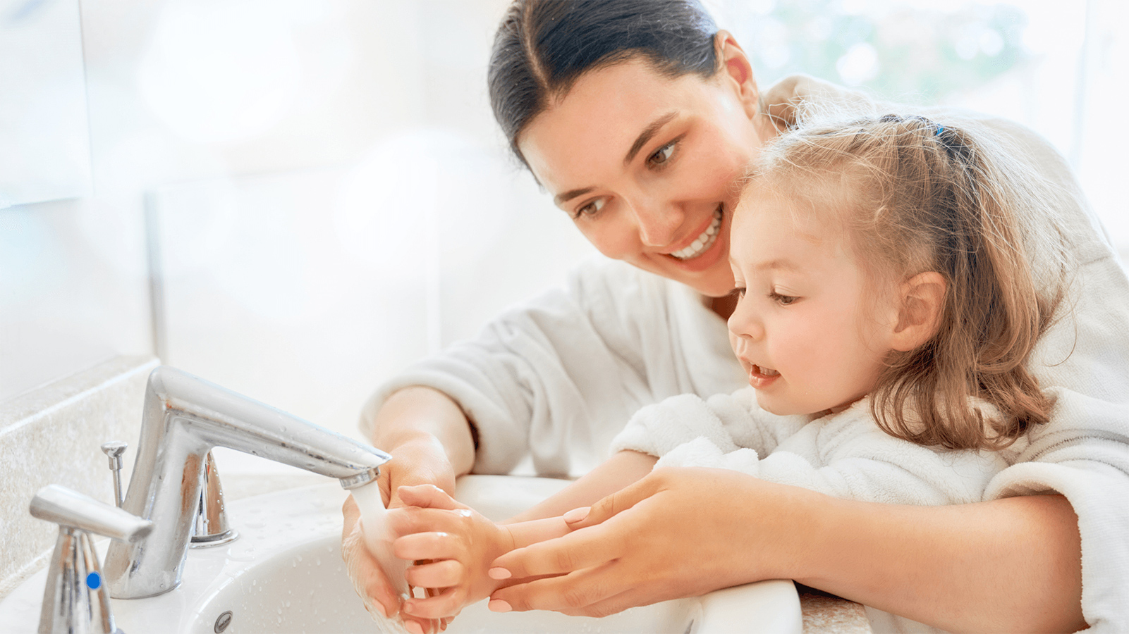 Mother helping her daughter wash her hands in the sink.