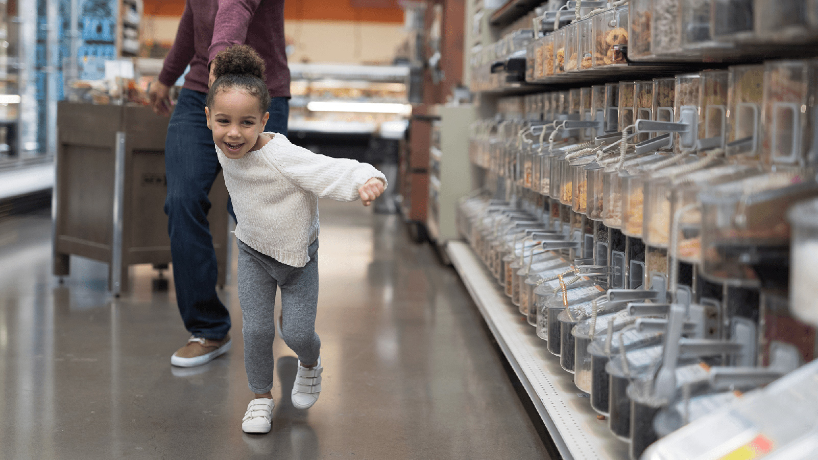 Little girl pulling her dad through a grocery store.