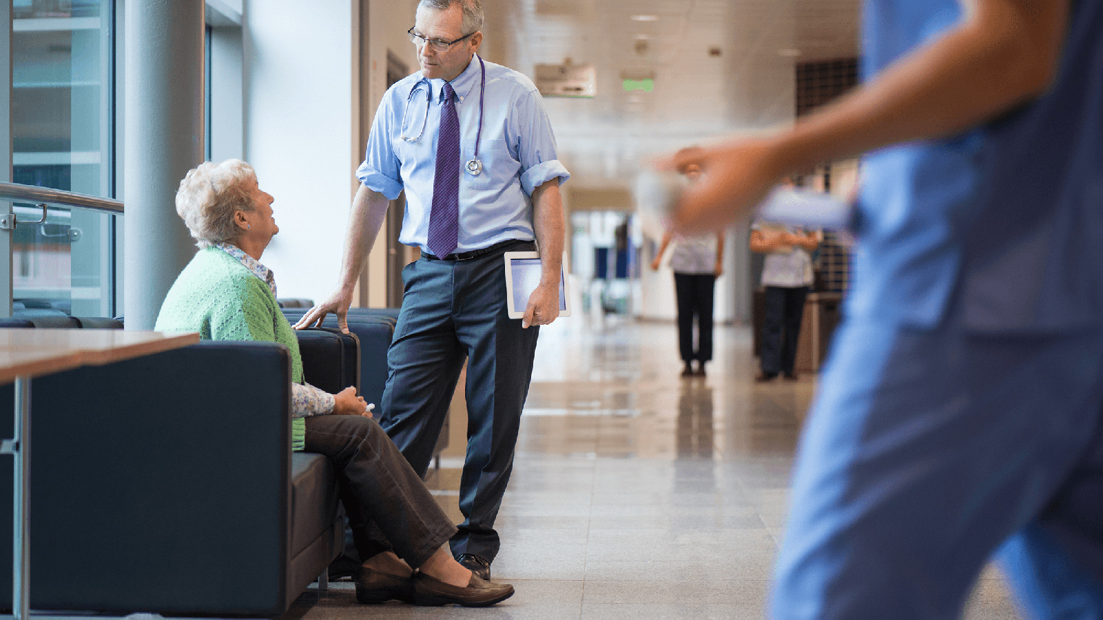 Medical professional speaking with a woman in the lobby of a medical building.