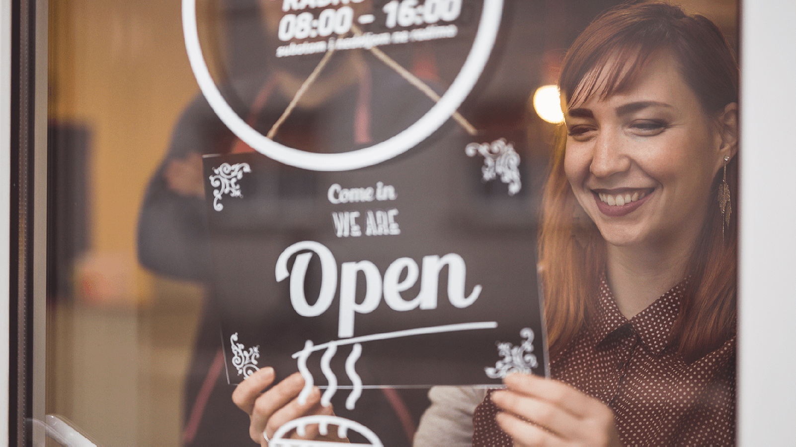 Woman smiling, putting an open sign in a storefront window.