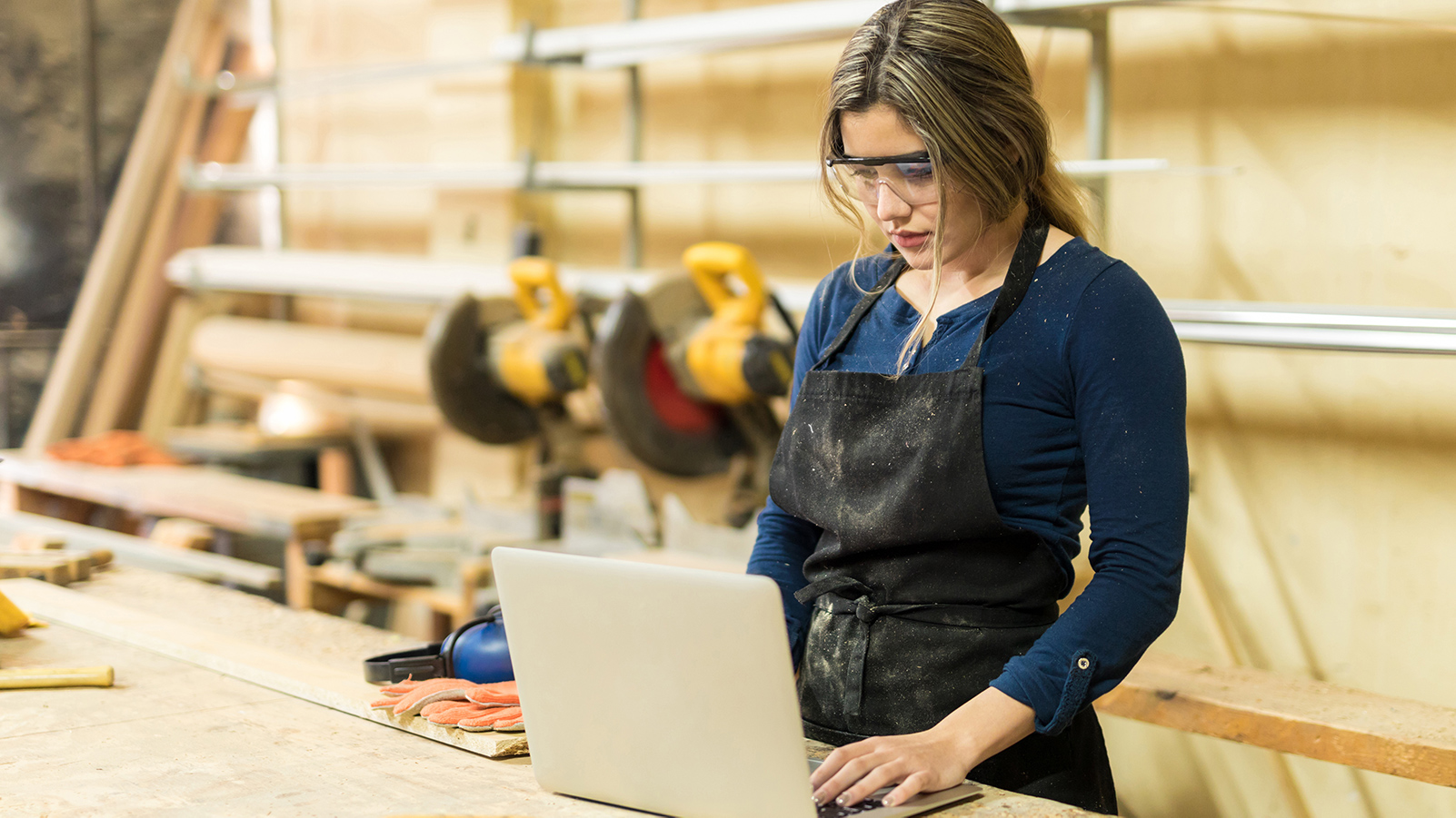 Woman using laptop in a woodshop.