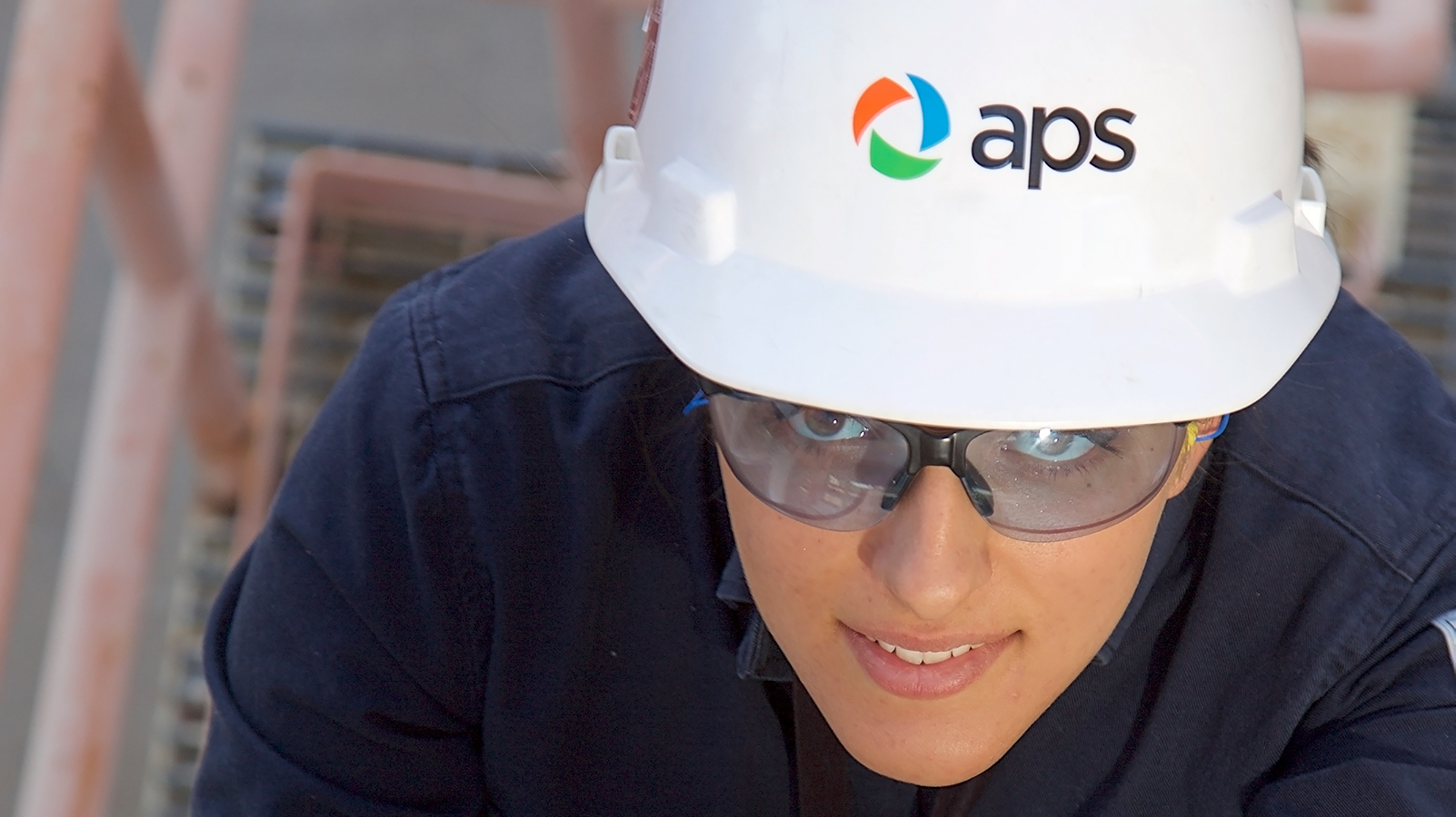 APS employee climbing a ladder.