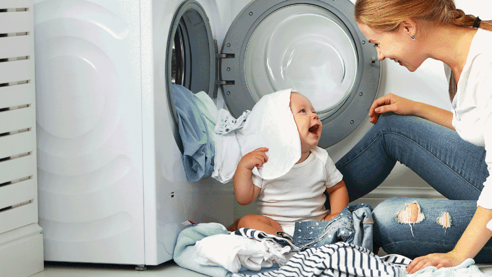 Mother and her baby smiling and playing in the laundry room.