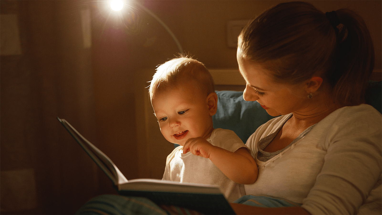 Mother reading a book to her baby.