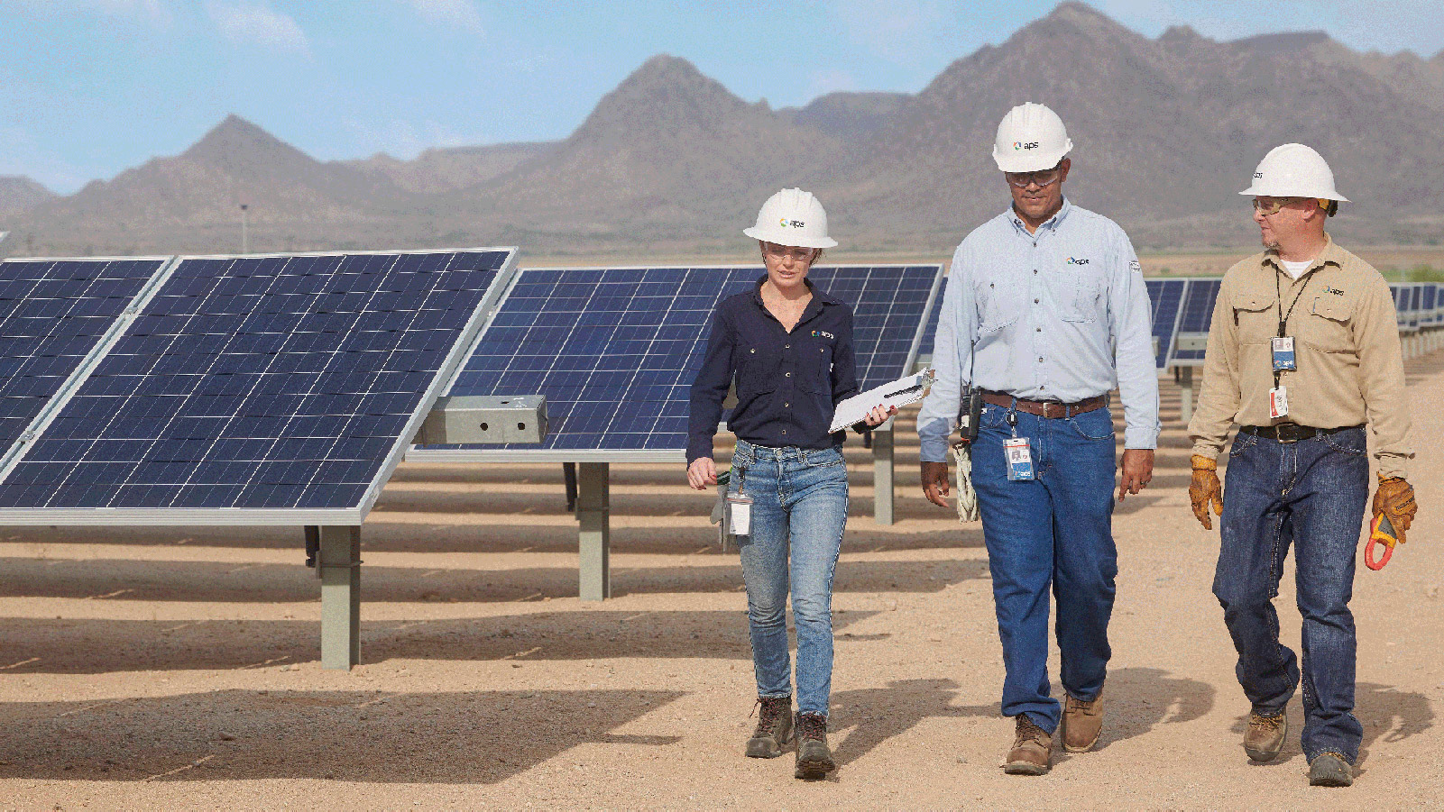 Three APS employees talking and walking through a solar field.