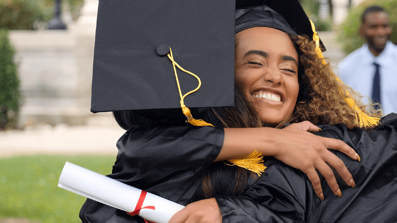 Two college graduates hugging in their caps and gowns.