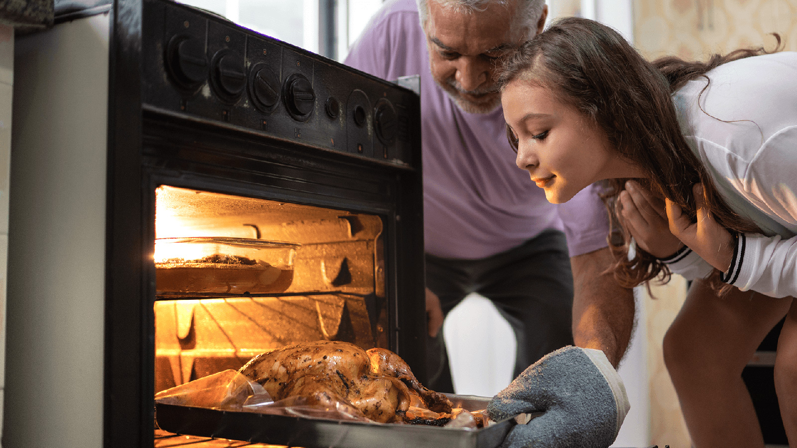 Father and his daughter cooking a turkey.
