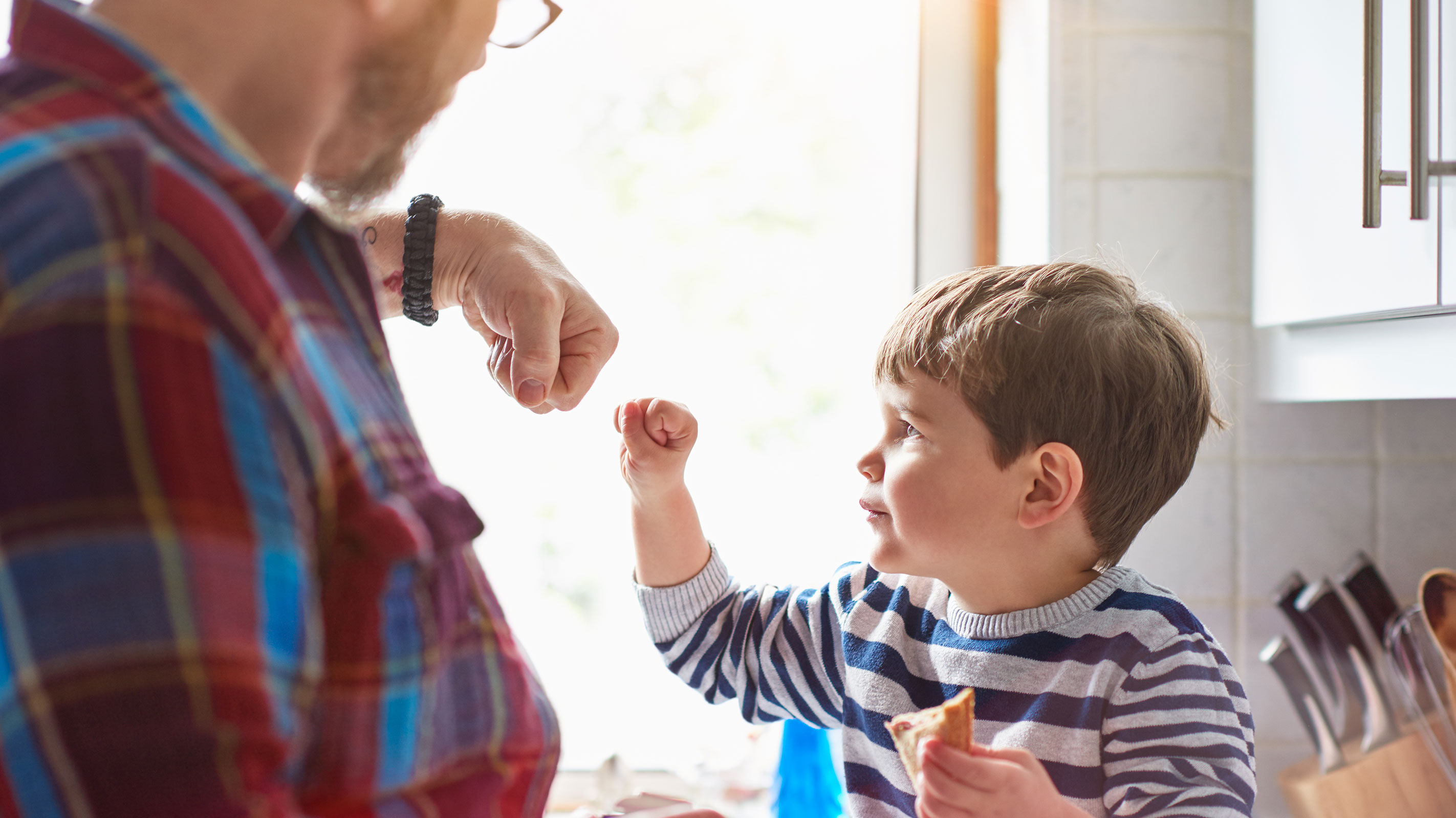 A little boy fist bumping his dad.