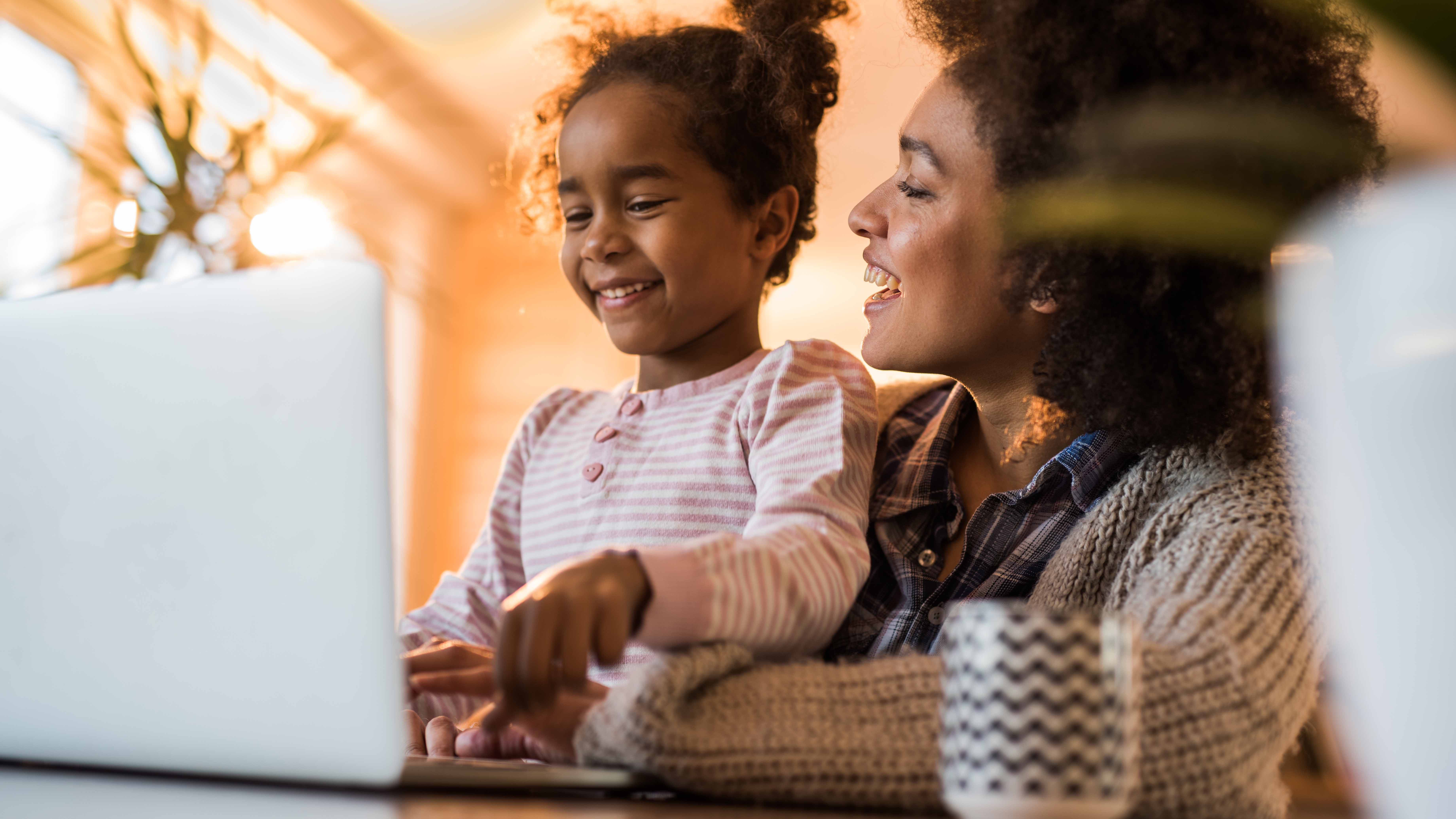 A little girl and her mom using a laptop.