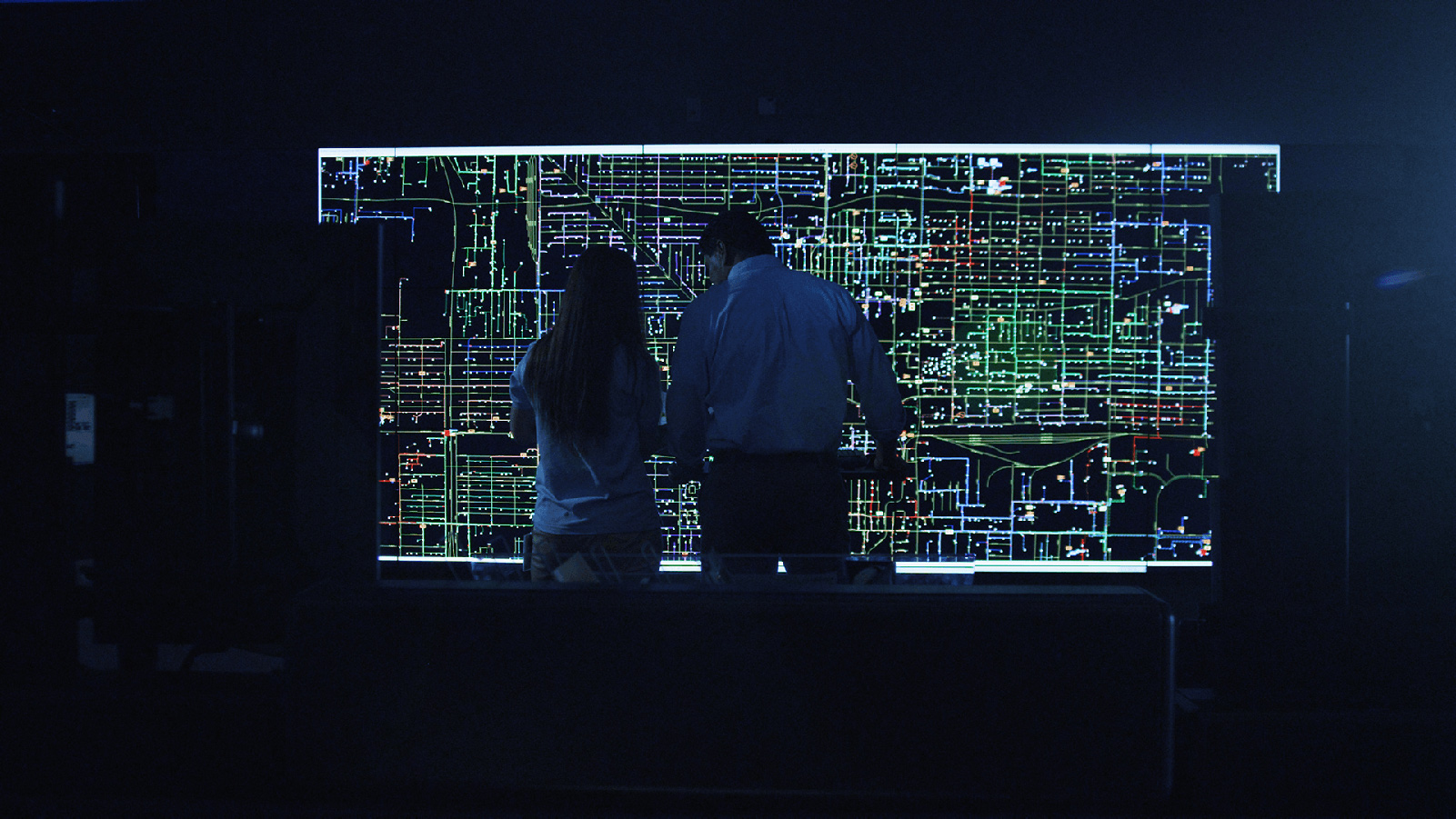 Two APS employees looking at a grid map in a dark room.