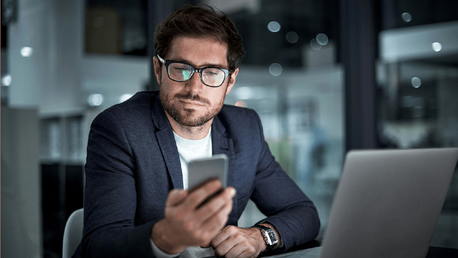 Man in glasses looking at his phone at a desk.