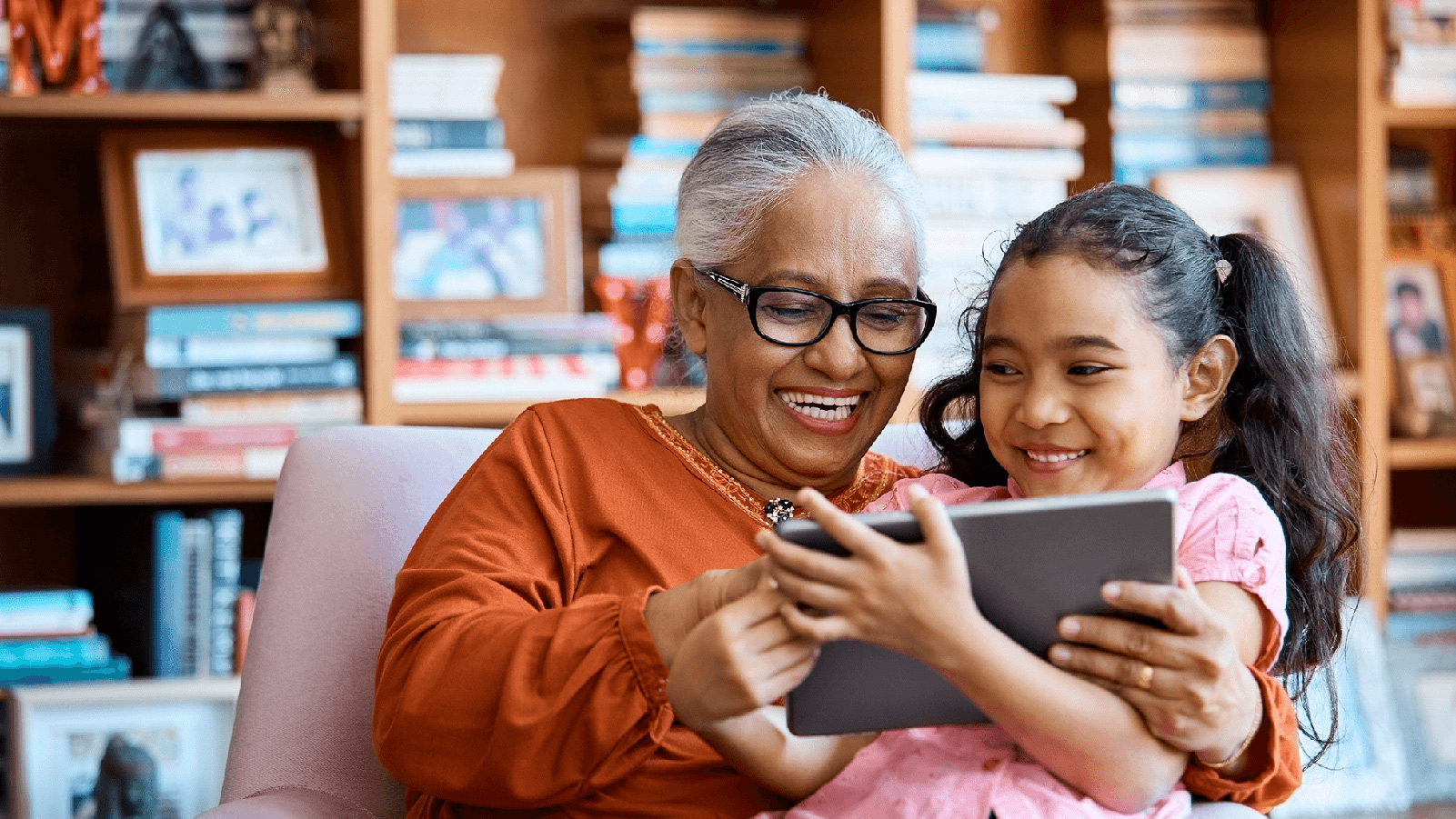 Grandma and her granddaughter smiling and looking at a tablet.