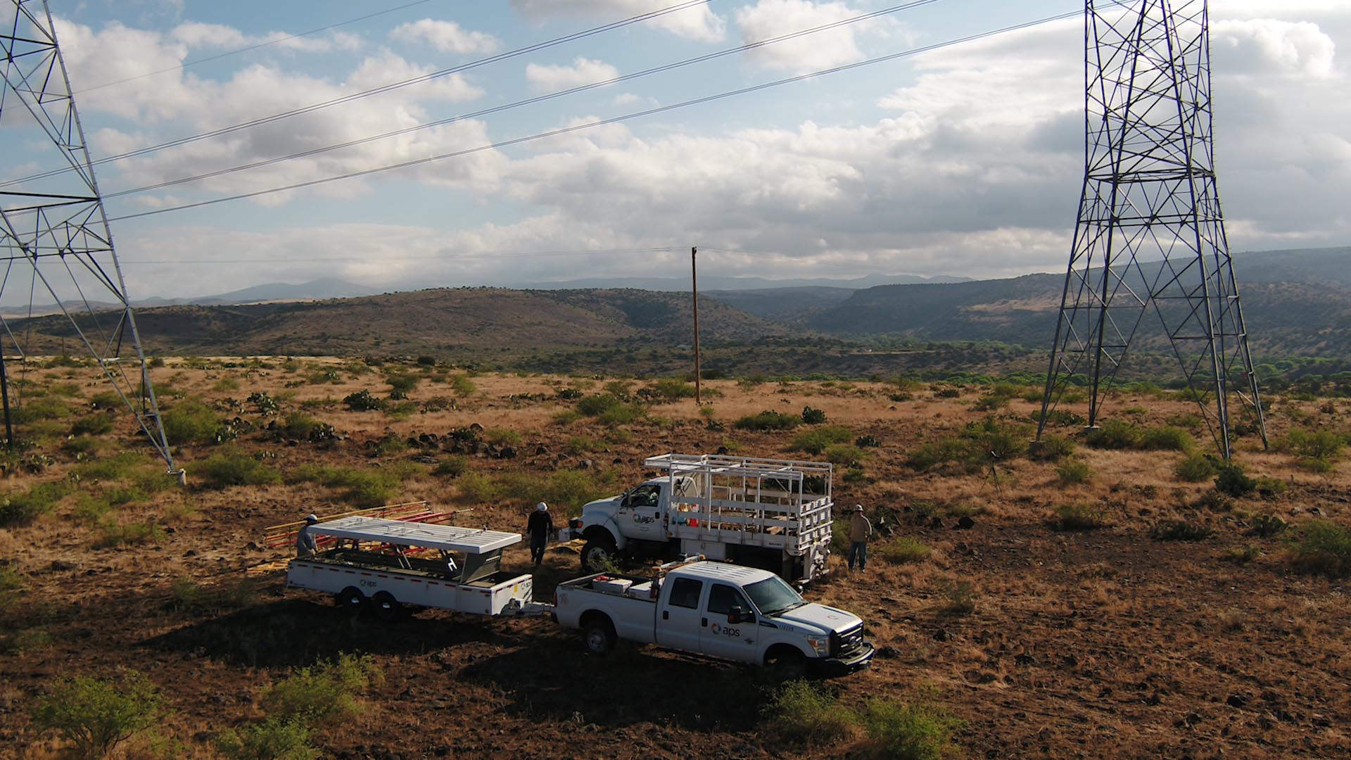 APS trucks below transmission tower in Arizona landscape.