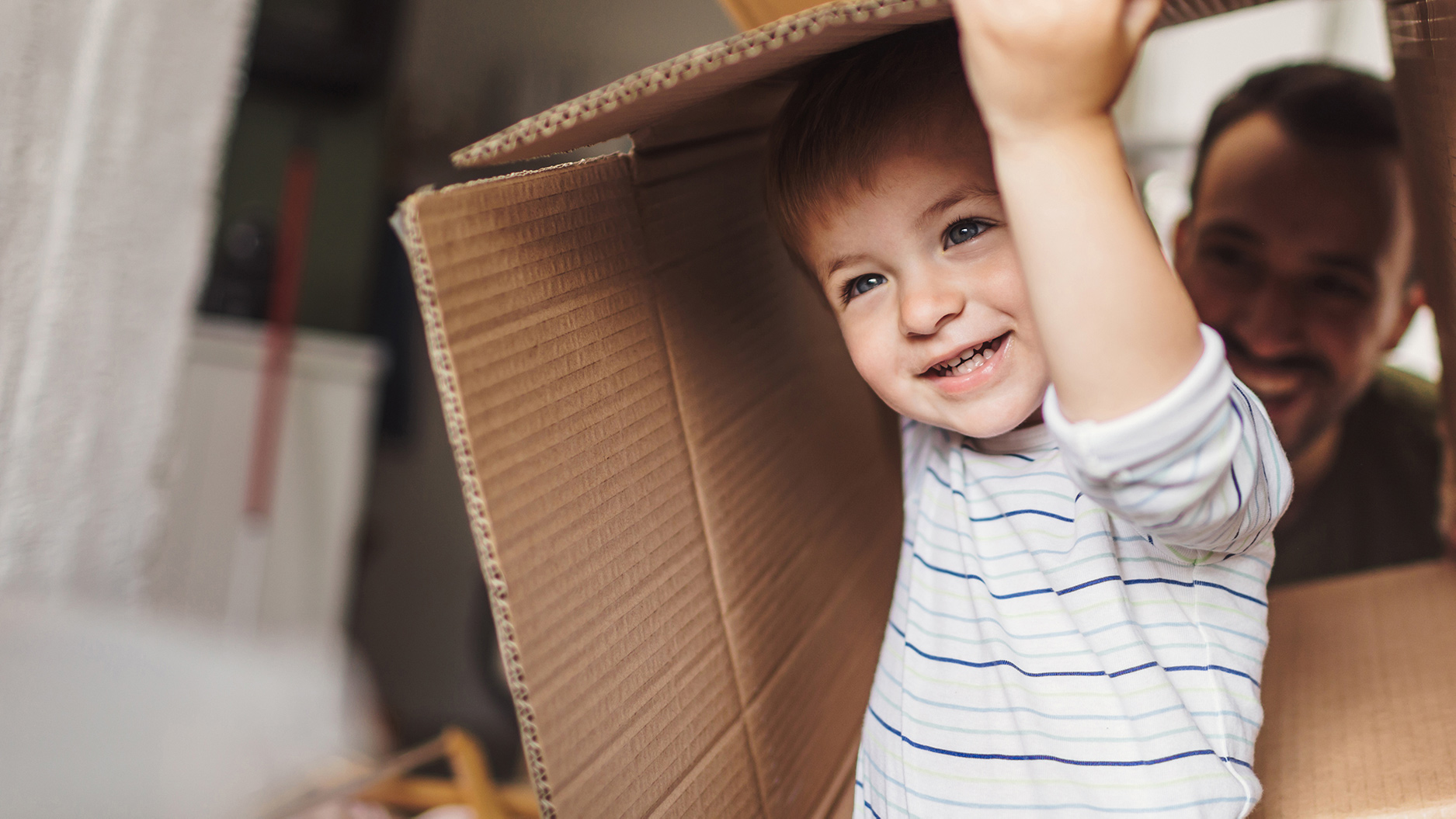 Father and son engage in imaginative play with a cardboard box.