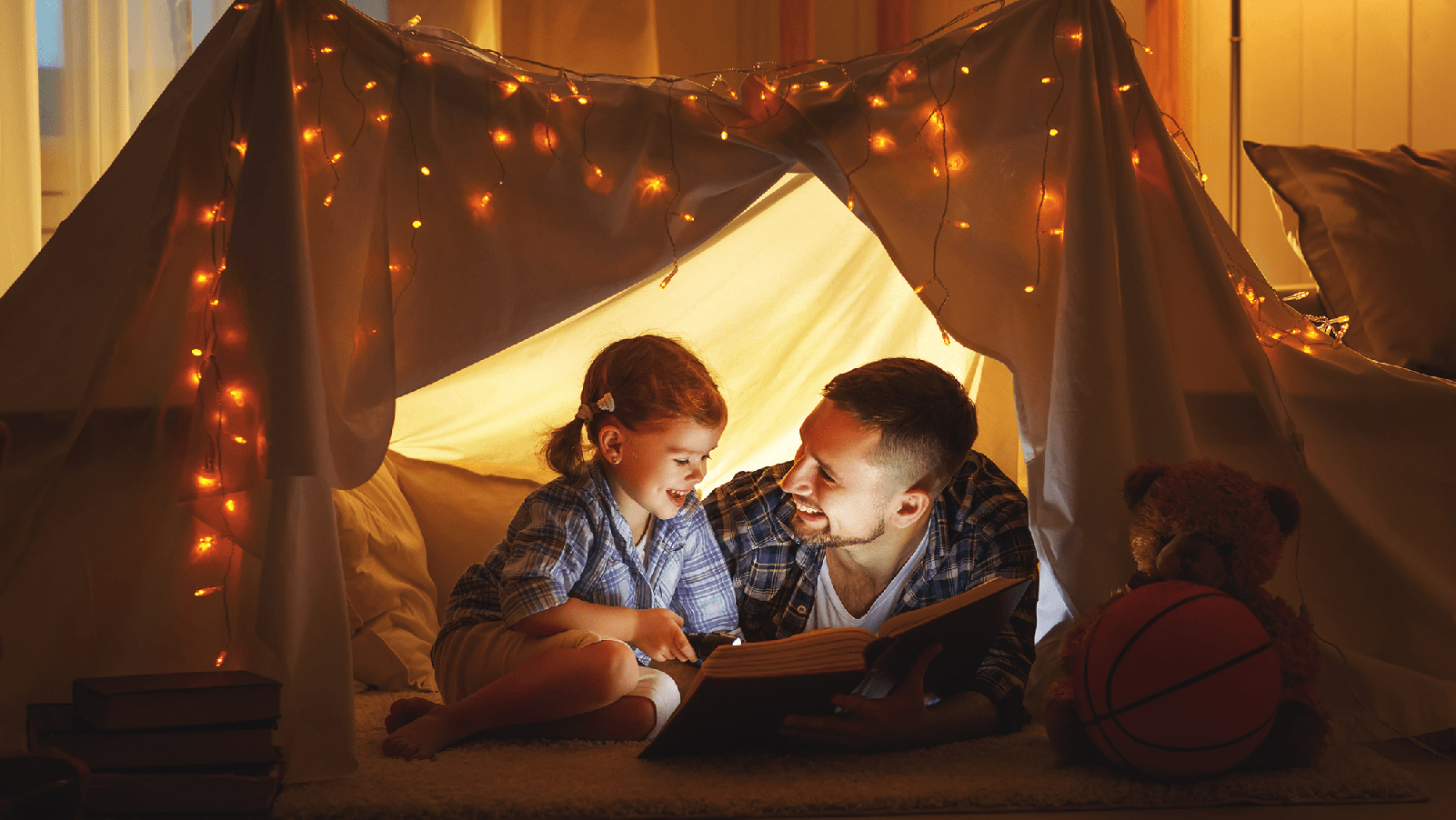 Father reading to his daughter in a blanket fort.