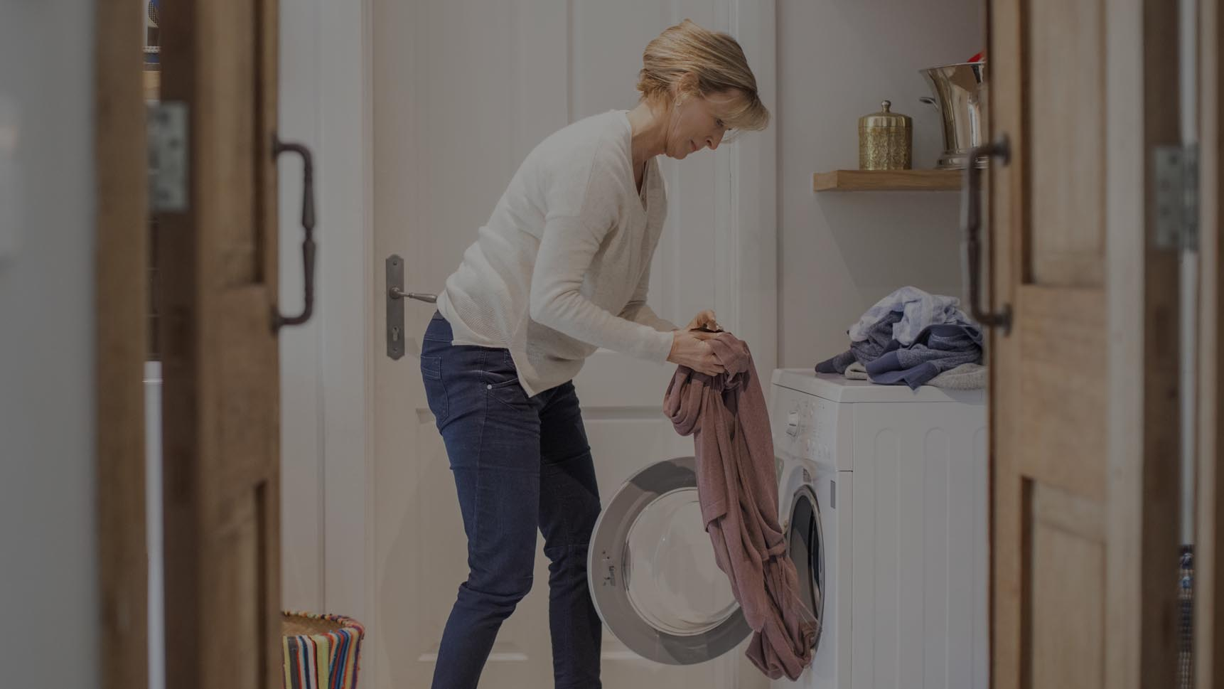 Woman pulling laundry out of washer