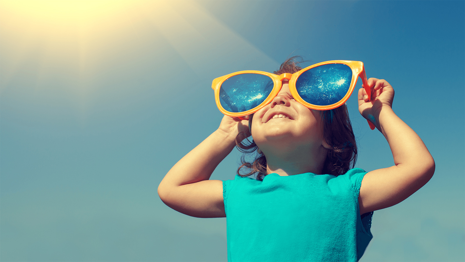 Little girl wearing oversized sunglasses on a bright sunny day.