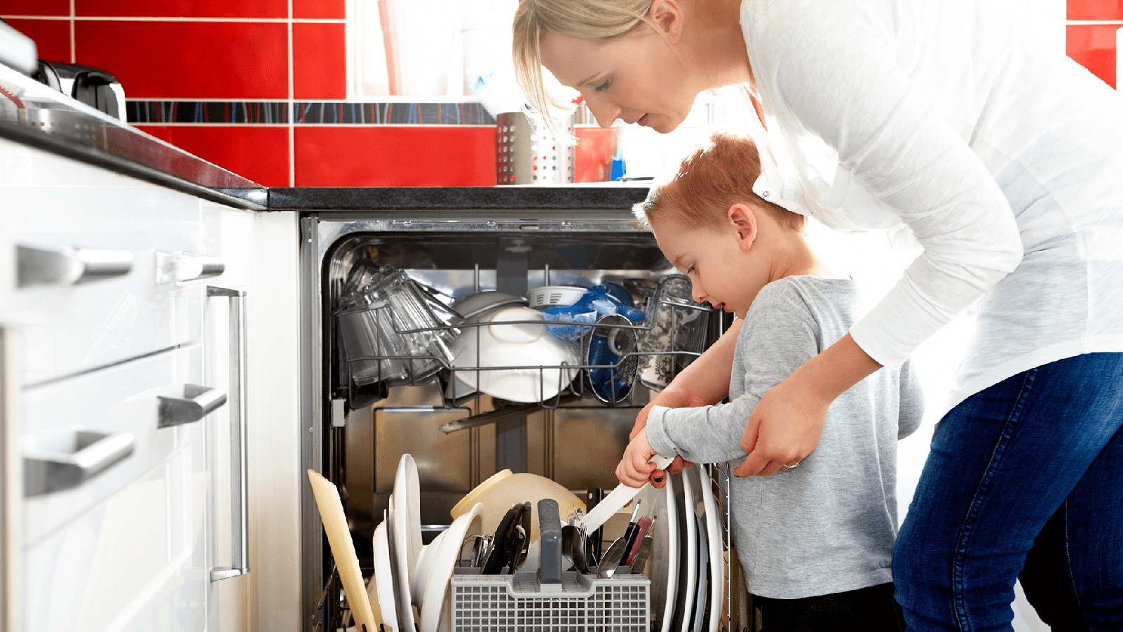 Little boy helping his mother load the dishwasher.