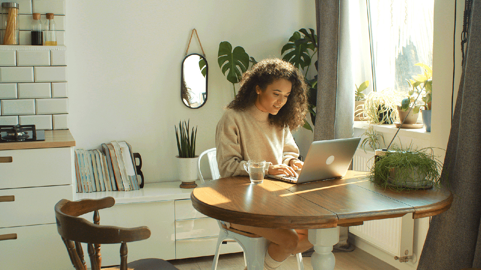 Woman working on a laptop in her sunny kitchen.