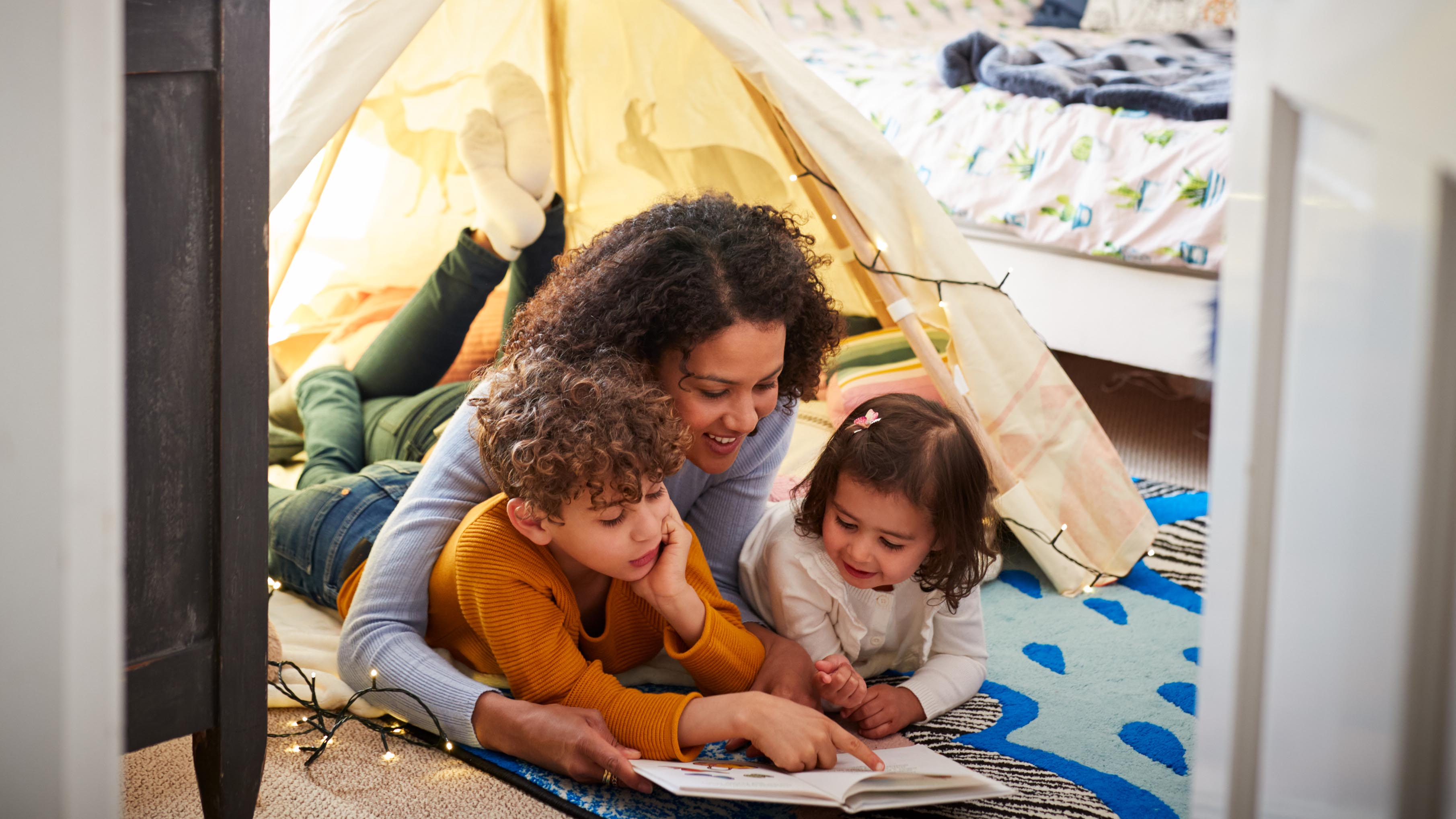 Family reading a book in a tent.