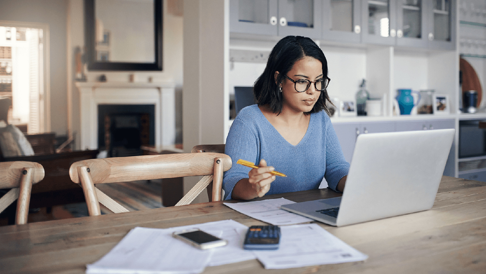Woman looking at her laptop on the kitchen table with paperwork.